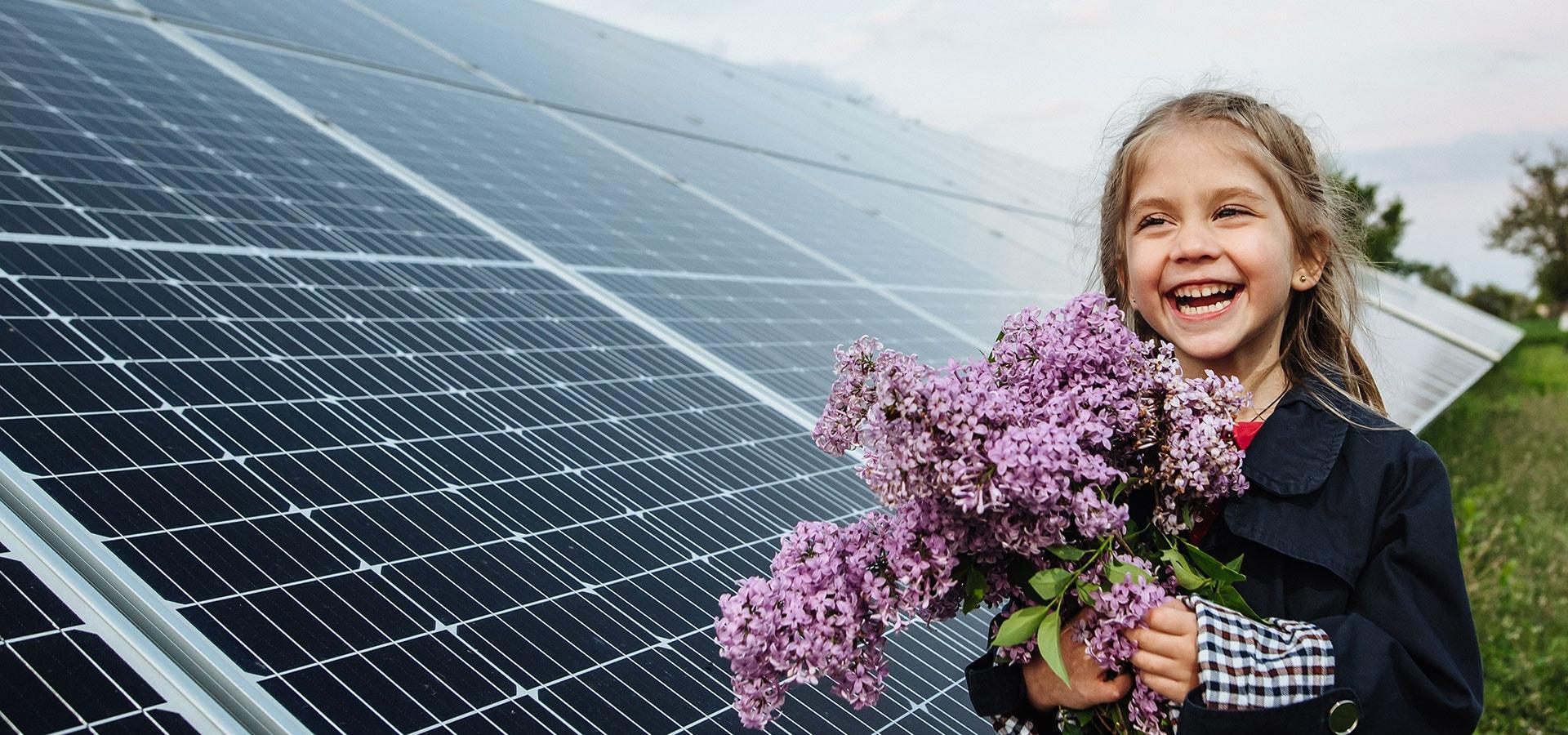 Lachendes Mädchen vor Photovoltaik-Anlage